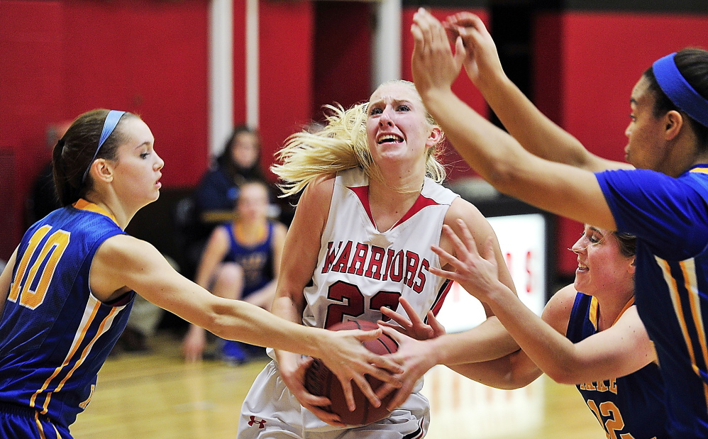 Alison Furness of Wells attempts to keep control of the ball Wednesday night while driving against Jordan Turner, left; Sarah Hancock, 12; and Tiana-Jo Carter of Lake Region. Furness scored 16 points as the Warriors rallied for a 44-36 victory in a game between undefeated teams.
