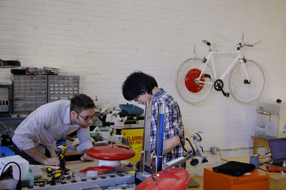 Mechanical and software engineer Julian Fong, right, and vehicle design engineer Jon Stevens work on a development to the Copenhagen Wheel.