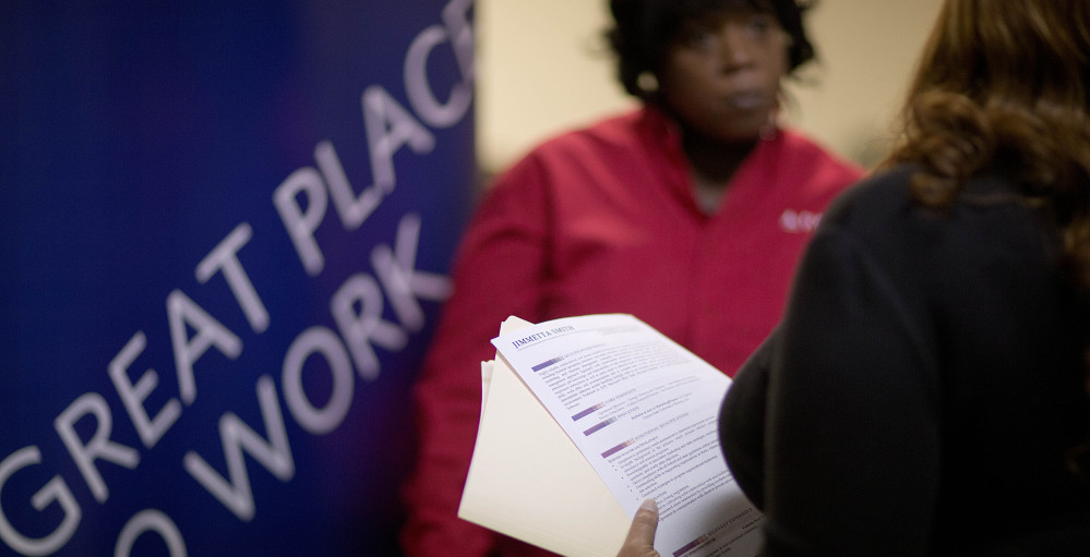 Jimmetta Smith of Lithonia, Ga., right, the wife of a U.S. Marine veteran, holds her resume while talking with Rhonda Knight, a recruiter for Delta Air Lines, at a job fair last month for veterans and relatives in Marietta, Ga.