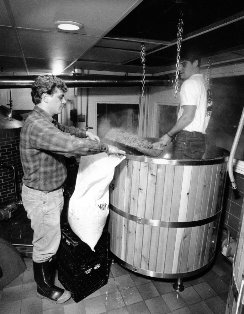 Stebbins holds open a sack as Pfeffer shovels spent grain from a mash tank at the Gritty's brewery in Portland in December 1988.