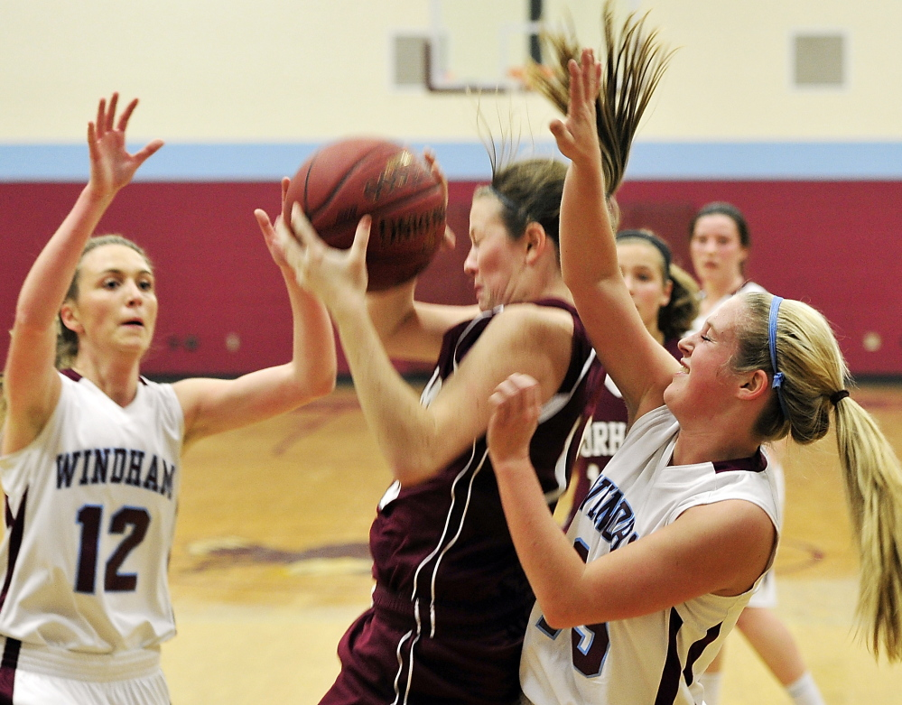 Jessica Rexrode of Gorham pulls down a rebound between Windham's Sam Frost, left, and Macy Mannette during an SMAA basketball game Friday night in Windham. Windham won in overtime, 40-39.