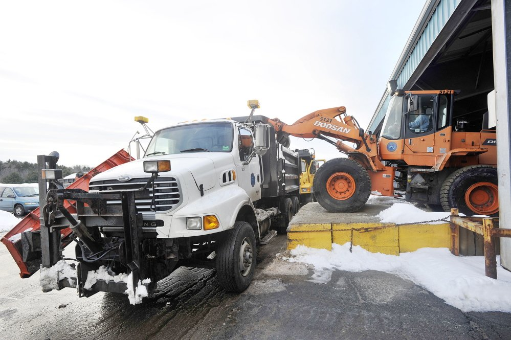 Portland Public Works employees load salt and sand trucks Thursday in preparation for expected precipitation this weekend.