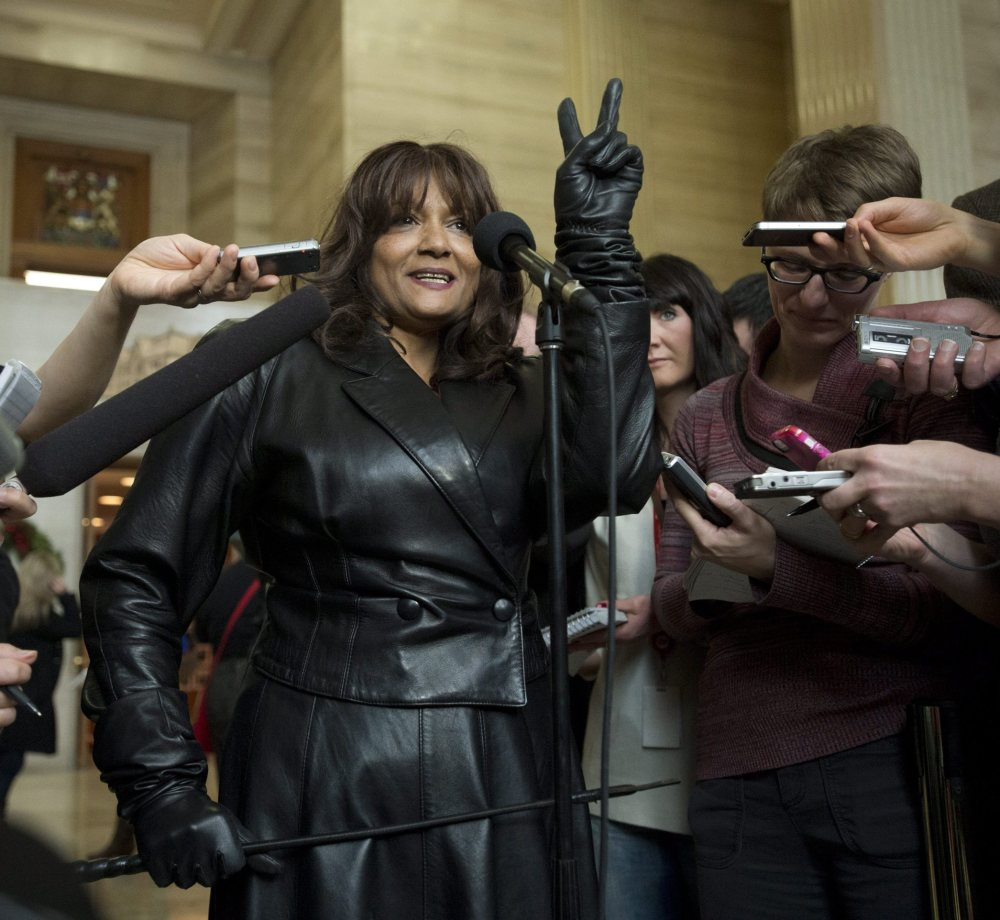 Terri-Jean Bedford, a retired dominatrix, gives a victory sign as she talks to reporters at the Supreme Court of Canada in Ottawa on Friday morning.