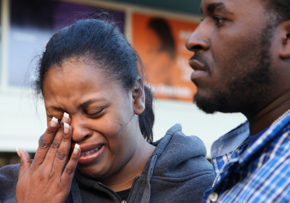 Nailah Winkfield, mother of 13-year-old Jahi McMath, wipes her face while speaking to reporters with her husband, Martin Winkfield, on Monday at Children's Hospital Oakland in Oakland, Calif. Jahi McMath remains on life support after undergoing a tonsillectomy.