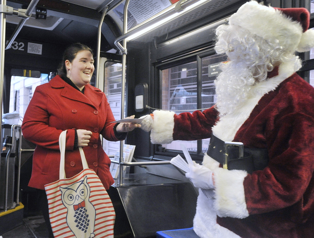 Britney Mitchell accepts a $100 bill from Secret Santa as she boards a Metro bus in Portland on Friday.