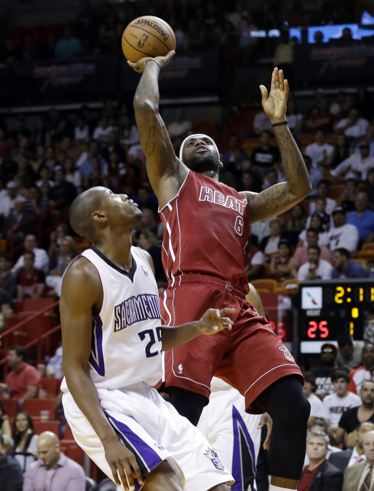 Miami's LeBron James shoots over Sacramento's Travis Outlaw in the first half of Friday's game in Miami, won by the Heat, 112-103.