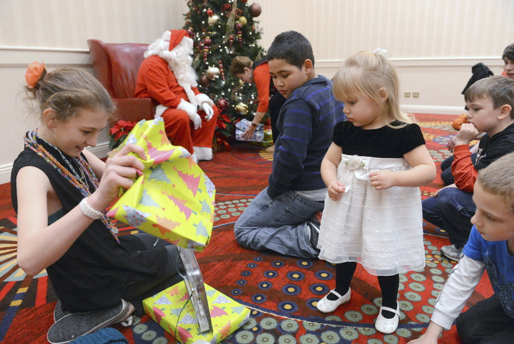 Children involved with Grandparents Raising Grandchildren Support Group unwrap gifts at the group's recent Christmas party at the Mystic Marriott in Groton, Conn.