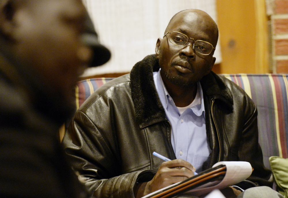 Mariano Mawein, chairman of a Maine Sudanese group, takes notes during a meeting of elders Saturday at a Portland church. Mawein said the elders agreed that South Sudan's president instigated the conflict and should resign immediately.