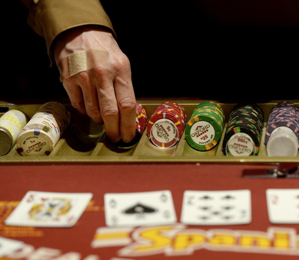 A dealer hands out chips at an Oxford Casino blackjack table. The table games at the casino bring in about $100,000 a month for the state Education Department.