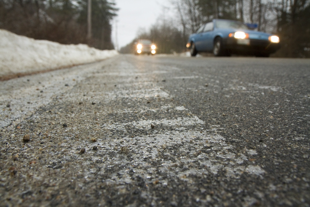 Ice builds up on the edge of the road as cars pass by on a treated, ice-free Saco Road in Standish on Sunday.