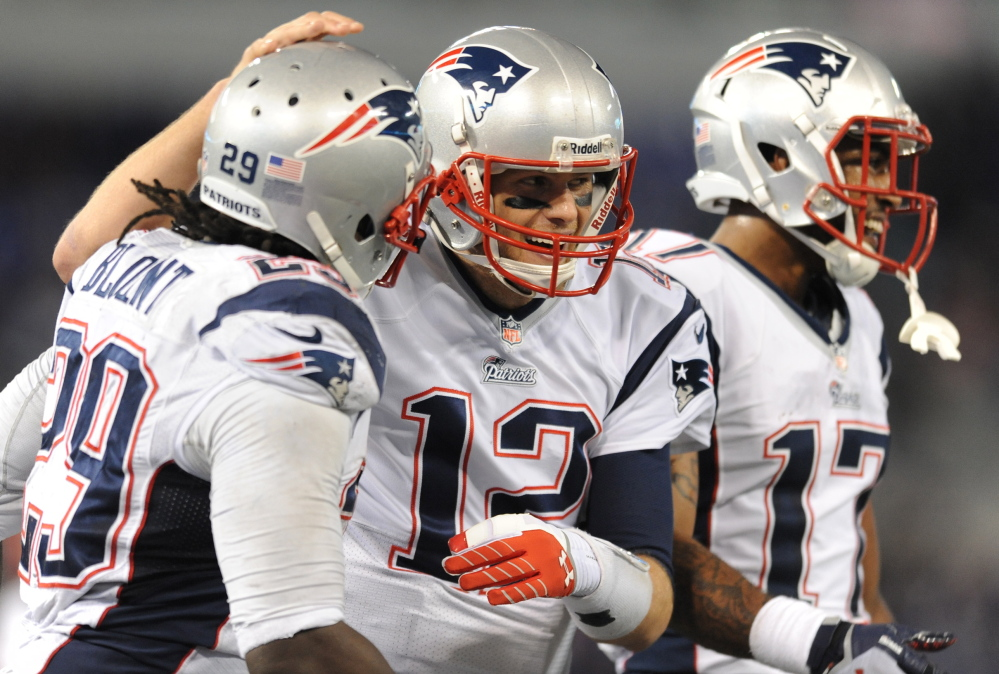 Tom Brady beams with teammates LeGarrette Blount, left, and Aaron Dobson after Blount scored one of his two touchdowns to put the Patriots well on their way to a rout over their AFC rivals Sunday afternoon in Baltimore.