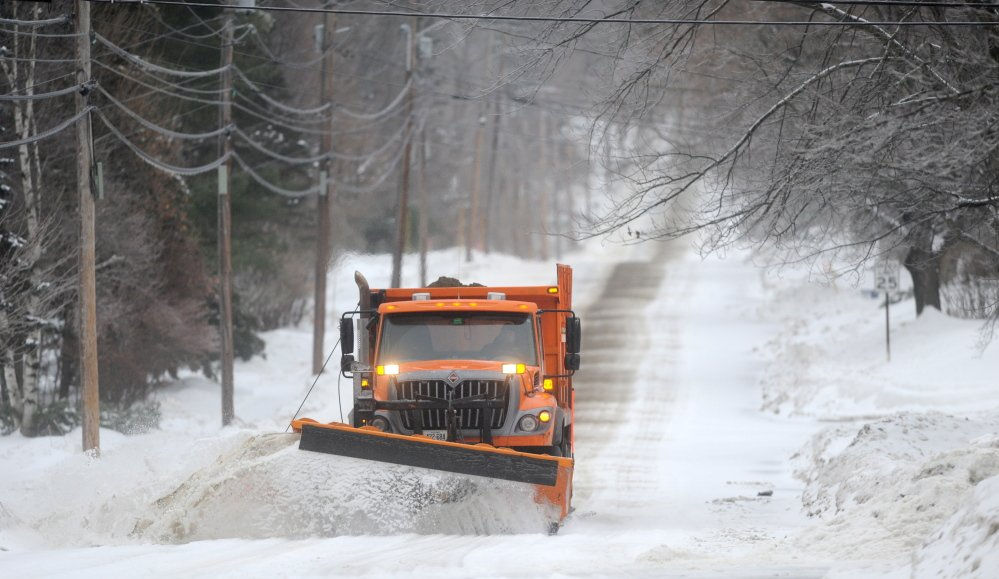 ICEY DICEY: A snowplow clears Mayflower Hill Drive in Waterville as a major ice storm rolls through the state on Sunday morning.