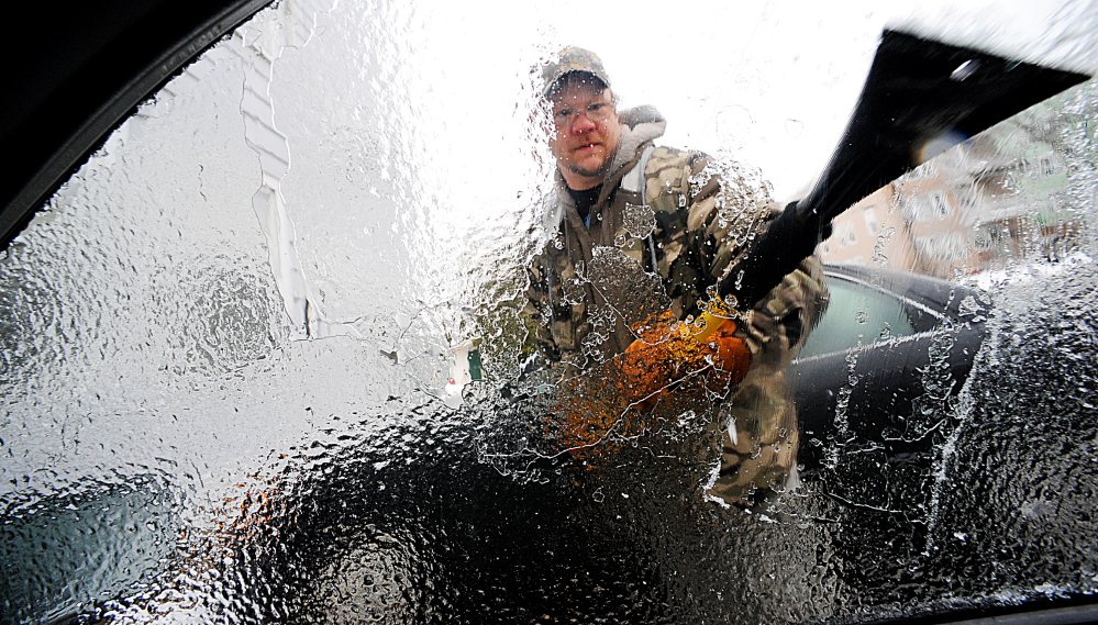 Charles Winslow clears ice off of his car in Lewiston on Sunday. Ice build-up on tree limbs brought down power lines in northern New England, leaving thousands of homes and business in Vermont and Maine without electricity.