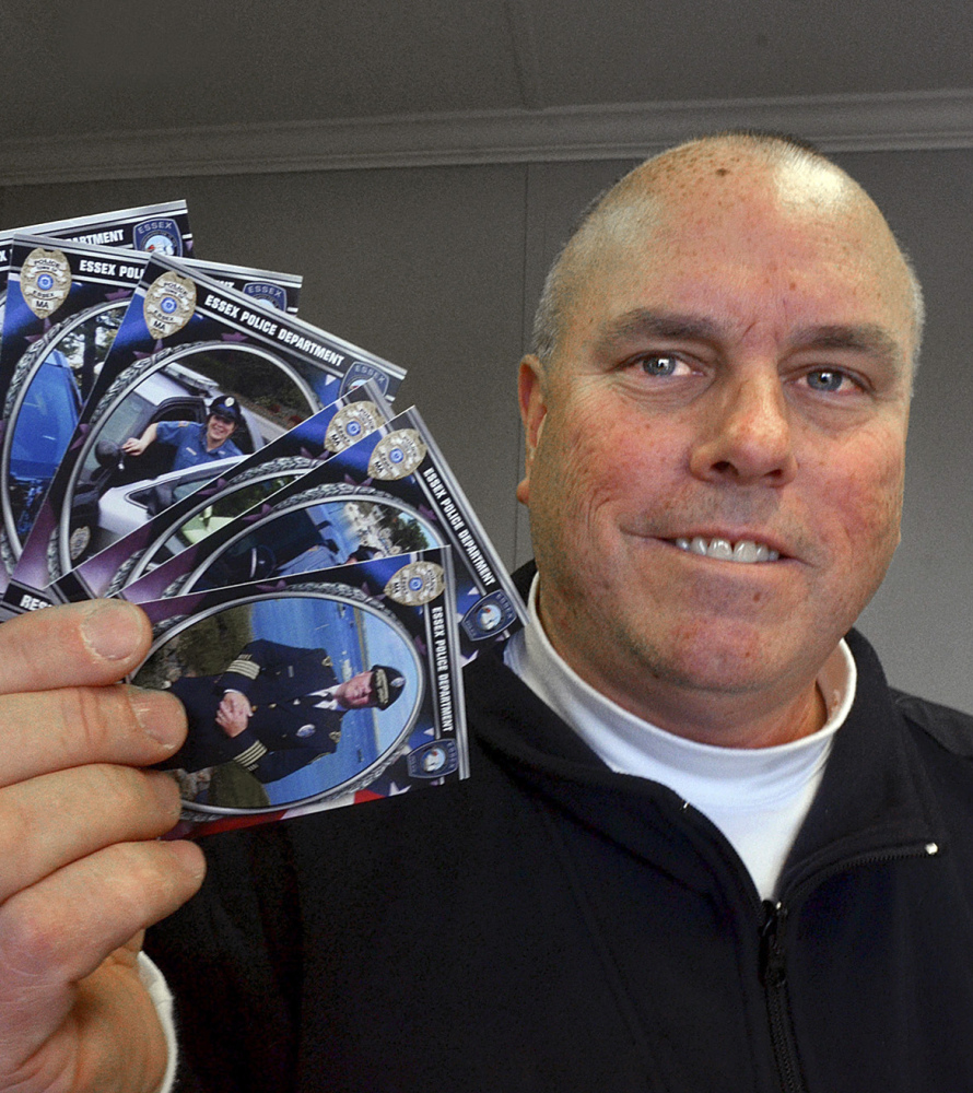 Police Chief Peter G. Silva holds trading cards depicting police officers at headquarters in Essex, Mass.