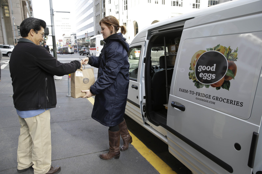 Good Eggs community dispatcher Vanessa Casey, right, hands an order to a Financial District customer in San Francisco. New online services are letting consumers buy fruits, vegetables, meats and artisan foods directly from local farmers and producers. Buyers can have their orders delivered or retrieve them at local pickup spots.