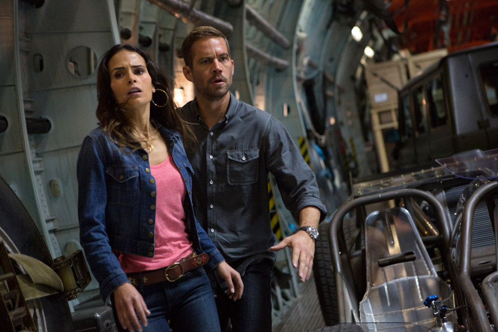 "This publicity image shows Jordana Brewster, left, and Paul Walker in a scene from ""Fast & Furious 6."" Shooting on ""Fast & Furious 7"" was about midway through when the 40-year-old Walker died in a car crash outside of Los Angeles."