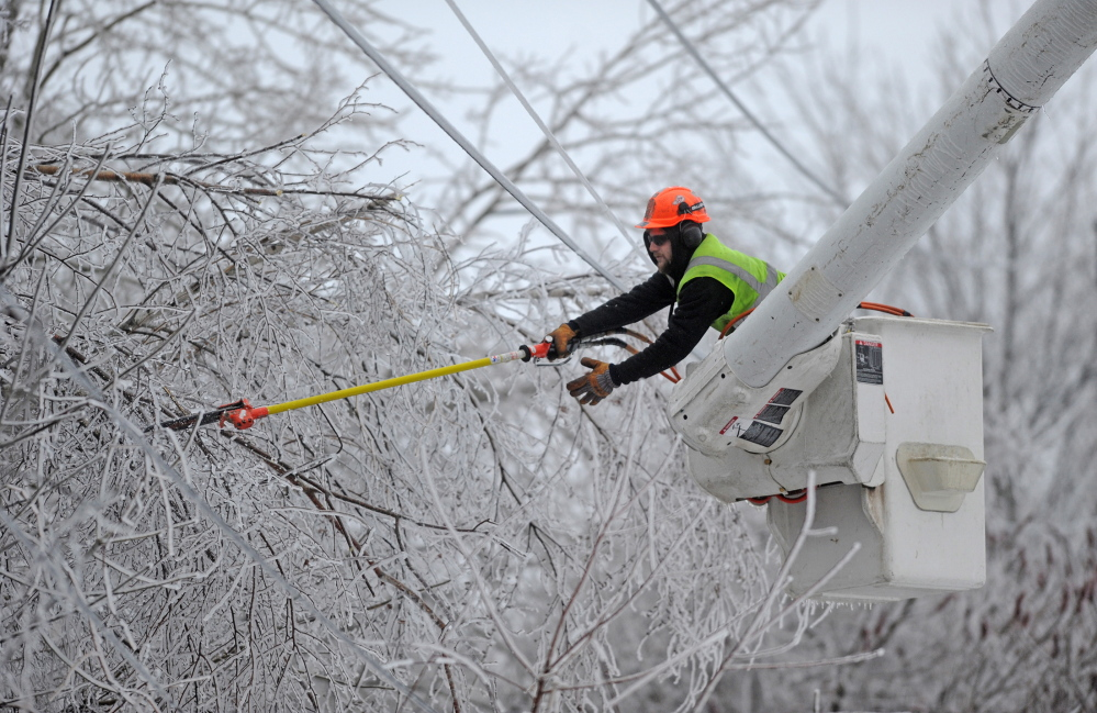 Andrew Powers, an arborist with Asplundh Tree Experts, clears power lines from iced branches along Mayflower Heights Drive in Waterville on Monday. Kennebec County led the way with about 34,500 outages, or more than half of all CMP customers in that county.