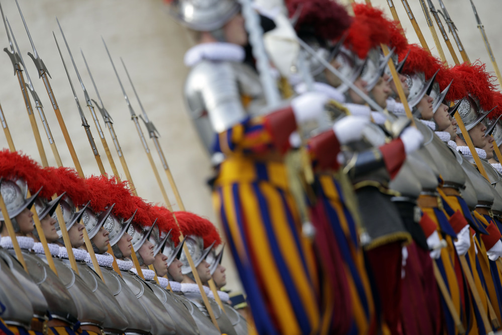 "Swiss guards stand at attention prior to the start of Pope Francis ""Urbi et Orbi"" (to the City and to the World) message he delivered from the central balcony of St. Peter's Basilica at the Vatican, Wednesday, Dec. 25, 2013. Pope Francis on Christmas day is wishing for a better world, with peace for the land of Jesus' birth, for Syria and Africa as well as for the dignity of migrants and refugees fleeing misery and conflict. Francis spoke from the central balcony of St. Peter's Basilica Wednesday to tens of thousands of tourists, pilgrims and Romans in the square below. He said he was joining in the song of Christmas angels with all those hoping ""for a better world,"" and with those who ""care for others, humbly."""