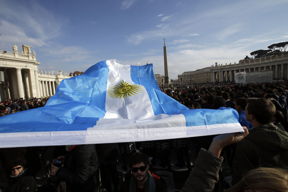 "An Argentine flag is waved by faithful prior to Pope Francis ""Urbi et Orbi"" (to the City and to the World) message he delivered from the central balcony of St. Peter's Basilica at the Vatican, Wednesday, Dec. 25, 2013. Pope Francis on Christmas day is wishing for a better world, with peace for the land of Jesus' birth, for Syria and Africa as well as for the dignity of migrants and refugees fleeing misery and conflict. Francis spoke from the central balcony of St. Peter's Basilica Wednesday to tens of thousands of tourists, pilgrims and Romans in the square below. He said he was joining in the song of Christmas angels with all those hoping ""for a better world,"" and with those who ""care for others, humbly."""