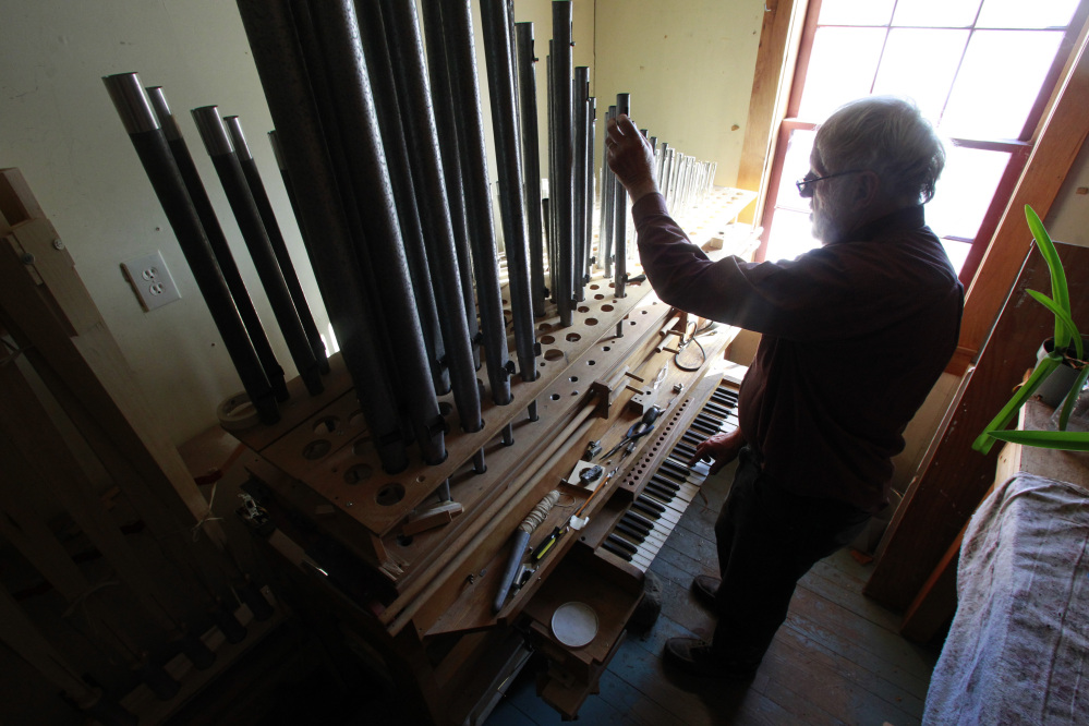 David Moore tunes the pipes on one of the organs he's restoring at his facility, a converted barn in Vermont.