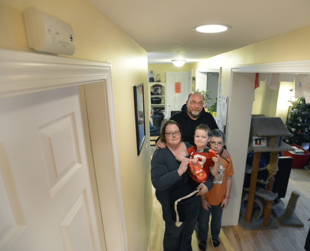 Heather and Bob Mills and their children, Cooper, 4, and Trenton, 11, stand in the hallway of their Biddeford home, where they installed another carbon monoxide detector, upper left, after the four were poisoned by the deadly gas in February.