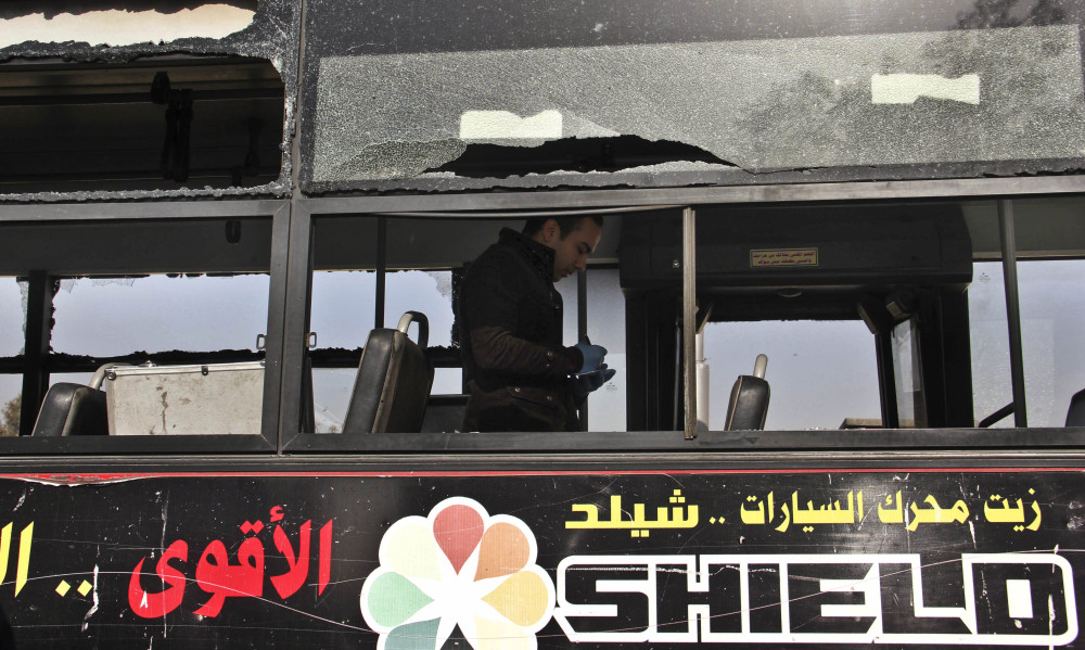 An Egyptian inspector takes notes Thursday inside a public bus that was hit by an explosion earlier in the day in the eastern Nasr City district of Cairo.