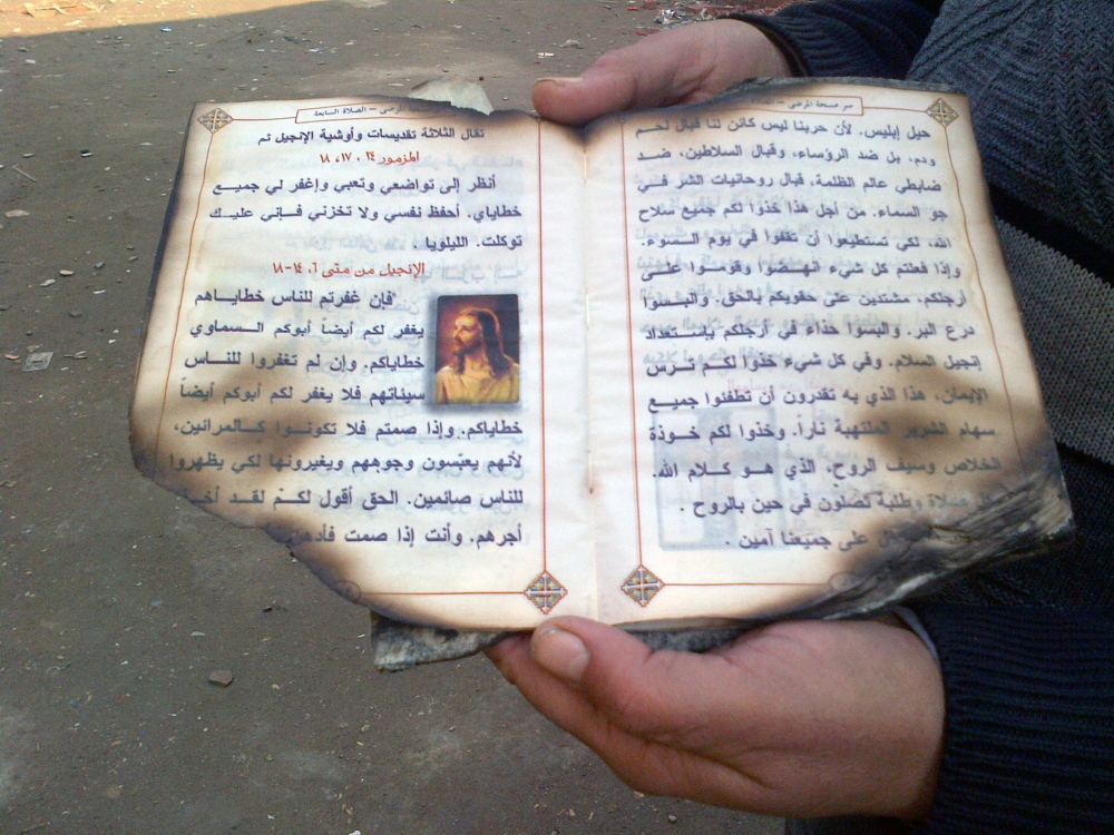 A parishioner holds a scorched Coptic prayer book, salvaged from an attack on the Church of the Archangel Michael in Kerdasa, Egypt, on Aug. 14.