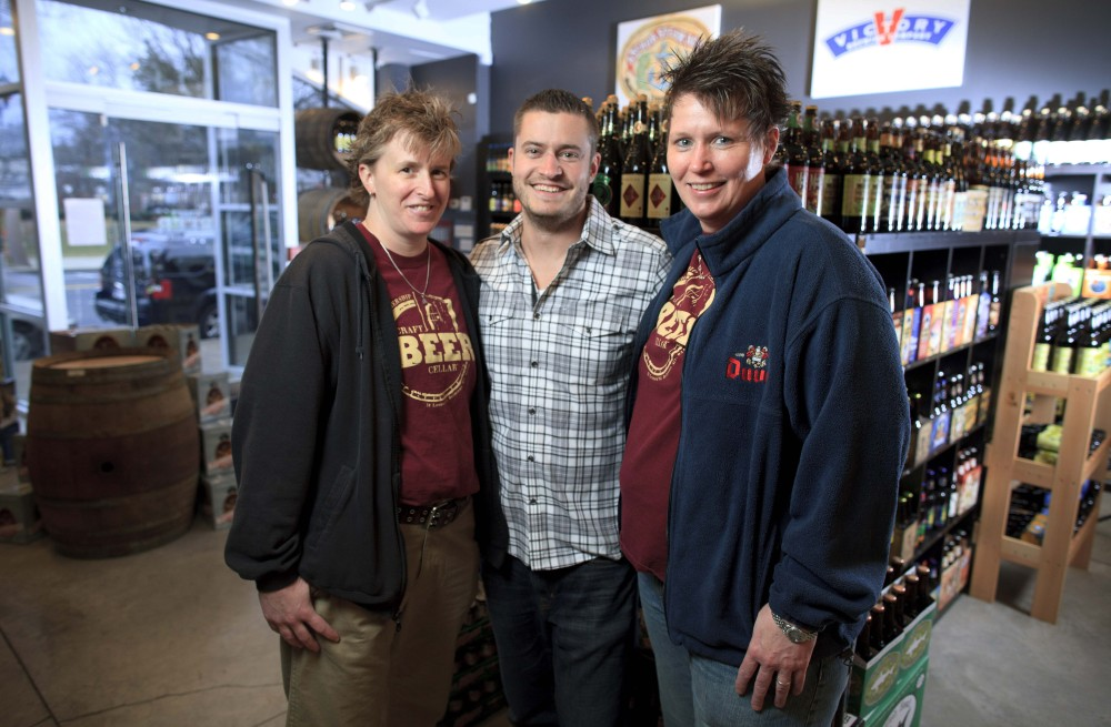 Craft Beer Cellar founders Kate Baker, left, and Suzanne Schalow, right, pose with Craft Beer Cellar store owner Brian Shaw in Newton, Mass. Beers there are organized by region, from Worcester to the West Coast, with an emphasis on local brews.