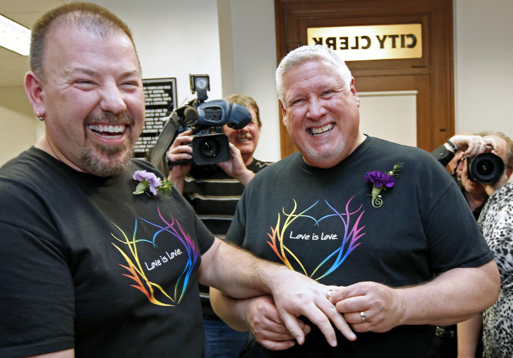 Steven Bridges, left, receives a wedding ring from Michael Snell at Portland City Hall in 2012. Crowds cheered them after they become the first same-sex couple to be married in the state.