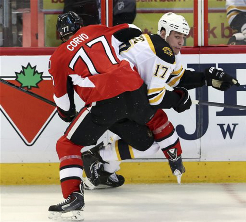 Boston Bruins' Milan Lucic is checked by Ottawa Senators' Joe Corvo during the first period of Saturday night's NHL game in Ottawa, Ontario.