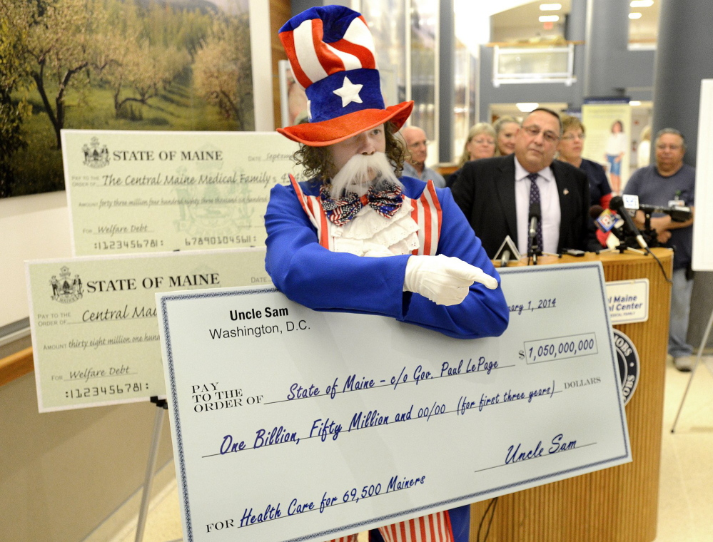 Paul Nickerson, dressed as Uncle Sam, disrupts a September media event where Gov. Paul LePage, background, presented a check to Central Maine Medical Center in Lewiston for backlogged Medicaid payments.
