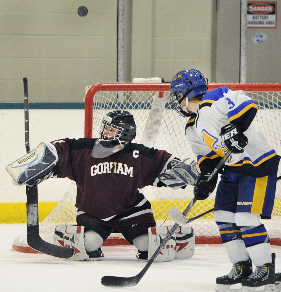Maddy Hamblen, the goalie for Gorham/Bonny Eagle, deflects a shot Saturday as Evie Clement of Falmouth looks for a possible rebound. Falmouth came away with a 5-0 victory in a schoolgirl hockey game at Family Ice.