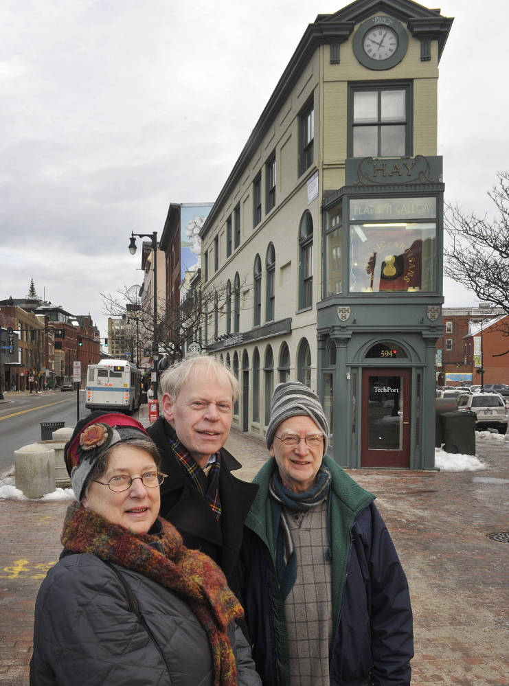 Greater Portland Landmarks will host a photography show at the Portland Public Library in January. Curators Susan Danly (left), Earle Shettleworth and Bruce Brown, who juried the exhibition, stand in front of Portland's Hay Building on Congress Street in Portland. Tuesday, December 24, 2013.