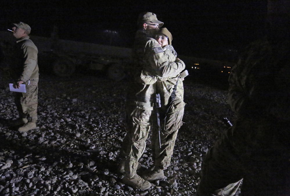 Sgt. Robert Kurka and his wife, Sgt. Jessica Kurka, both of Durham, embrace as Robert prepares to leave with the convoy late on Dec. 20. South of Kabul, the convoy would run into snow, which adds to the danger of such trips because snow can effectively hide IEDs.