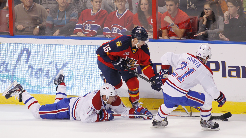 Florida Panthers center Aleksander Barkov battles against Montreal Canadiens defenseman Andrei Markov, left, and right wing Brian Gionta during the first period of Sunday's game in Sunrise, Fla., won by the Panthers, 4-1.