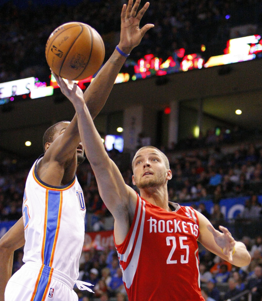 Houston's Chandler Parsons drives to the basket around Oklahoma City's Kevin Durant during the first quarter of Sunday's game in Oklahoma City, won by the Thunder.