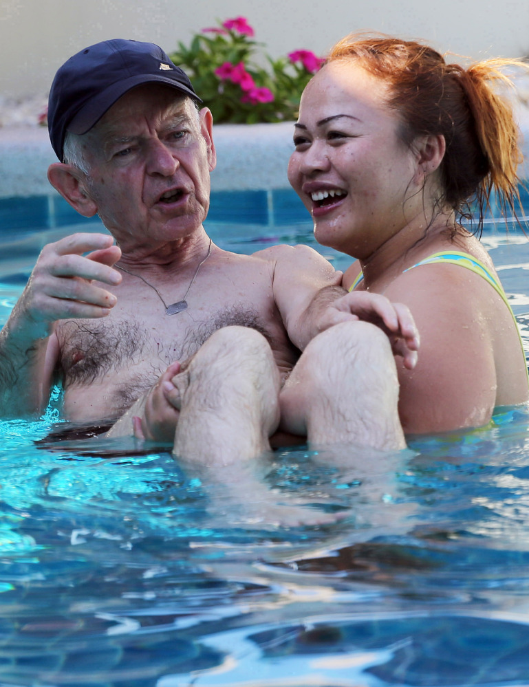 A Thai caretaker assists Gerhard, an Alzheimer's patient from Switzerland, at the Baan Khamlangchay care center. A new facility is due to open next year