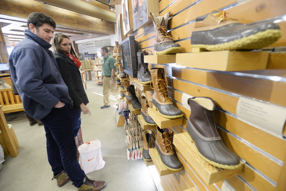 Ian Rothkopf and Jaci Daigneault, both of Boston, look over boots while shopping Monday at L.L. Bean in Freeport. Several popular sizes are out of stock because of the harsh winter.