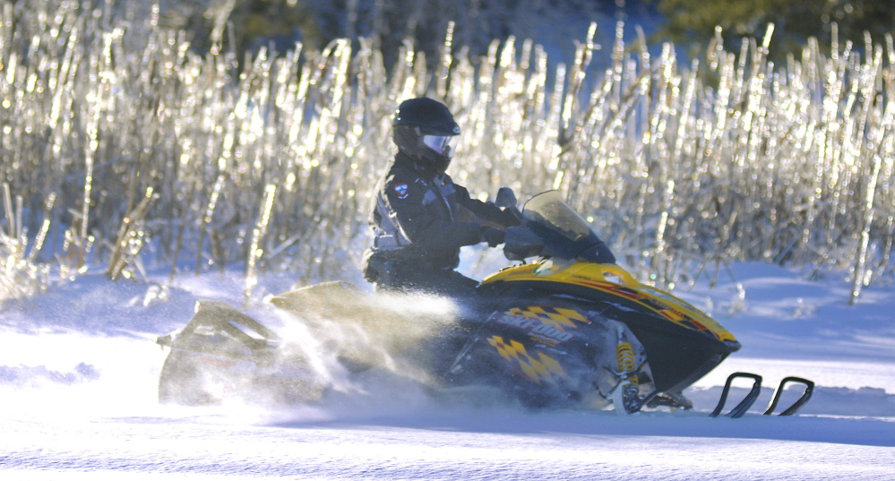 Warden Steve Allarie patrols a snowmobile trail Moday in Manchester. Inland Fisheries and Wildlife is asking sledders to be cautious this winter to reduce accidents.