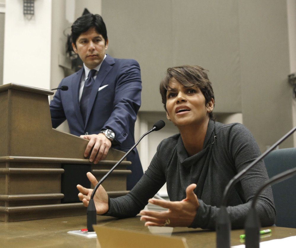 In this Aug. 13, 2013, file photo, actress Halle Berry urges lawmakers to support a bill that would limit the ability of paparazzi to photograph children of celebrities and public figures, at the Capitol in Sacramento, Calif. The bill, by state Sen. Kevin de Leon, D-Los Angeles, left, was approved by the Legislature and signed by Gov. Jerry Brown, is one of the more than 800 new laws to take effect Jan. 1.