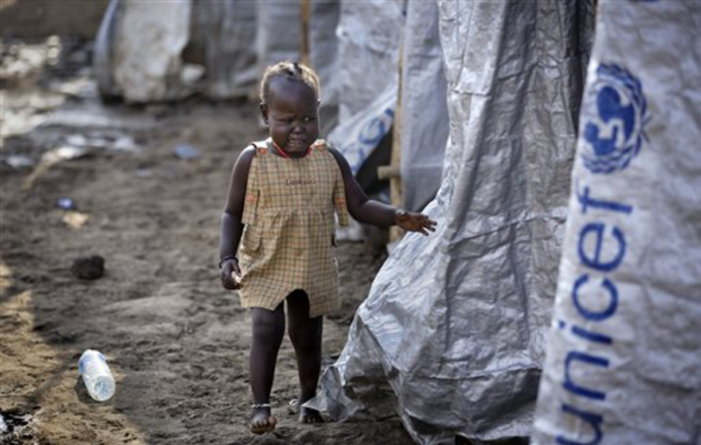 A young displaced girl starts crying after the relative she was with disappears into a row of latrines, at a United Nations compound which has become home to thousands of people displaced by the recent fighting, in the capital Juba, South Sudan Sunday.