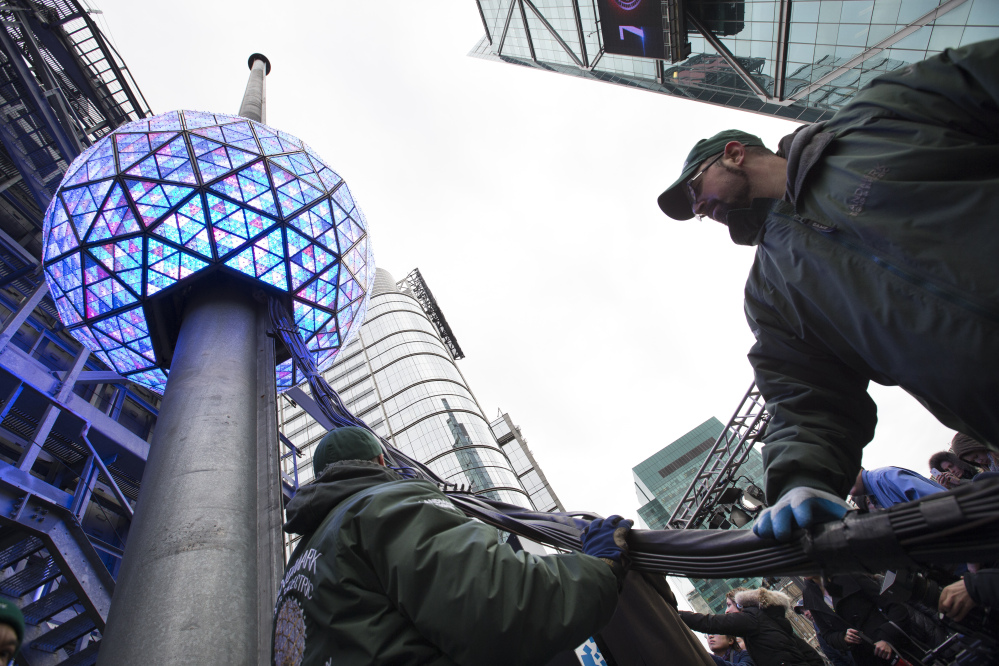 Workers handle cables attached to the New Year's Eve ball during a test atop the 1 Times Square building, Monday, Dec. 30, 2013, in New York. The iconic 11,875-pound geodesic sphere covered in 2,688 Waterford Crystal triangles will descend a 130-foot pole to mark the stroke of midnight during the annual Times Square celebration.