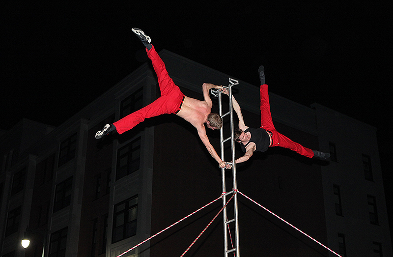 David Graham, left, and Tobin Remick balance on top of a ladder during the First Friday Art Walk on Congress Street.