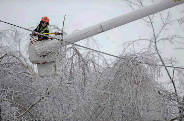 Andrew Powers, an arborist with Asplundh Tree Experts, clears power lines from iced-over branches along Mayflower Heights Drive in Waterville on Monday.