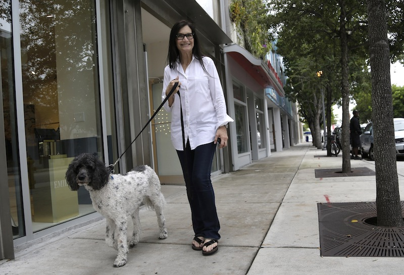 Gallery owner Deborah Sponder walks her dog in the Design District neighborhood of Miami. Fully 20 percent of U.S. adults become rich for parts of their lives, wielding outsized influence on America's economy and politics.