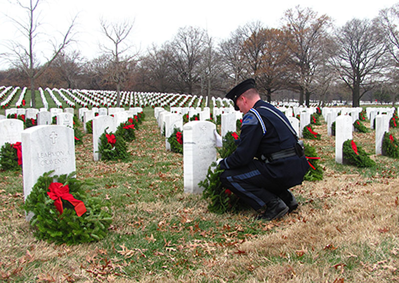 Portland Police Officer Kevin Haley pauses as he rests a wreath against the headstone of his brother, William Haley, at Arlington National Cemetery in Virginia. Kevin Haley is an advisory board member of Wreaths Across America, the Maine-based nonprofit that shipped 143,000 wreaths to Arlington. He is a coach of the Cheverus High School swim team, which sent more than a dozen members to Virginia for the wreath-laying ceremonies.
