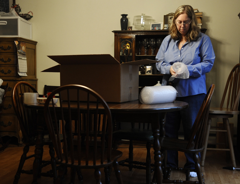 Leslie Lynch, 52, packs up belongings in her dining room in Glastonbury, Conn., on Dec. 23. Lynch, who lost her job last year, is moving out of her home of 21 years because she can no longer afford the mortgage payments.