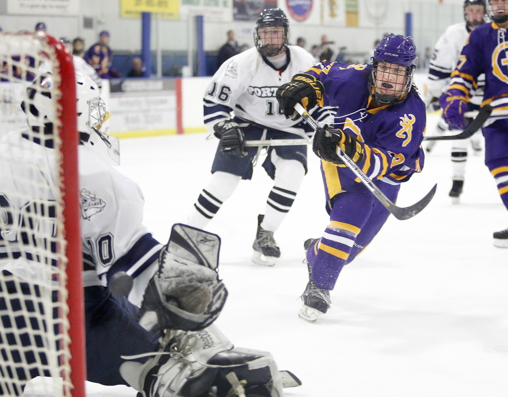 Conor Ryle of Cheverus lifts the puck over the glove of Portland/Deering goalie Sam Segal to score during the second period of the City Cup hockey game at Portland Ice Arena on Wednesday. The Stags won the cup with an 8-0 victory.