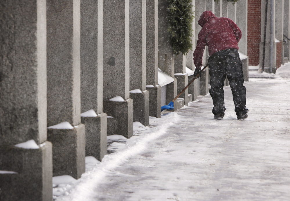 Jeremy Kempton shovels snow on a sidewalk along Commercial Street in Portland on Thursday. More than a foot of snow was predicted for coastal areas.