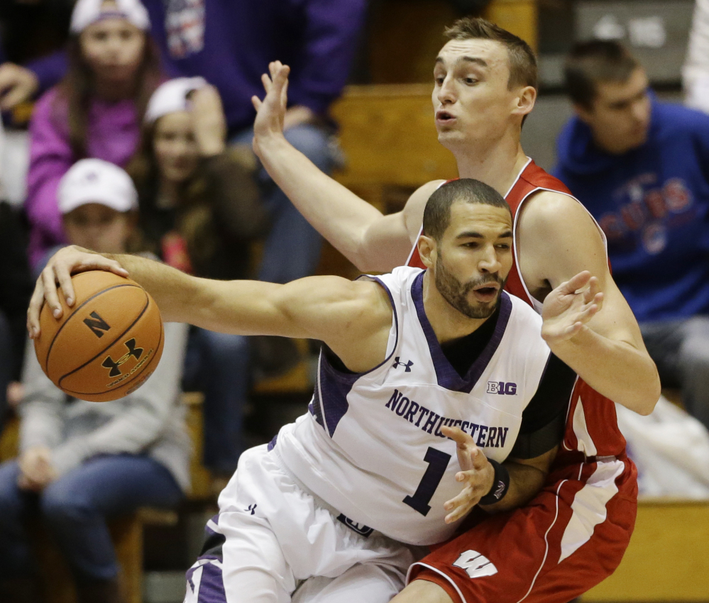 Drew Crawford of Northwestern looks for a way around Sam Dekker of Wisconsin during their Big 10 opener Thursday night at Evanston, Ill. Wisconsin improved to 14-0 with a 76-49 victory.